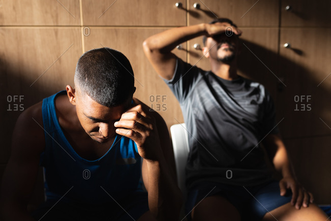 Two mixed race male football players wearing sports clothes sitting in changing room during a break in game, resting holding their heads being disappointed.
