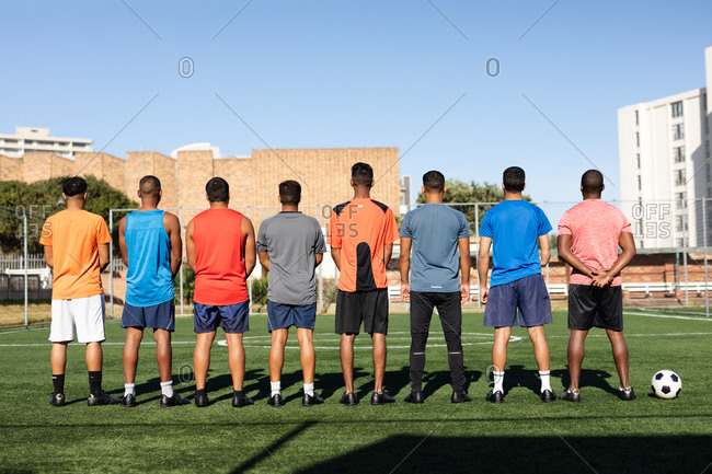 Rear view of multi ethnic group of male five a side football players wearing sports clothes training at a sports field in the sun, standing in a row before a game with ball next to them.