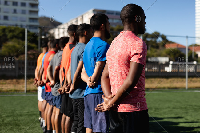 Multi ethnic group of male five a side football players wearing sports clothes training at a sports field in the sun, standing in a row before a game.