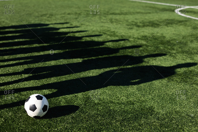 Shadow on grass pitch of group of male football players training at a sports field in the sun, standing next to each other ball next to them.