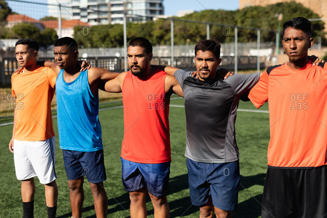 Multi ethnic group of male five a side football players wearing sports clothes training at a sports field in the sun, standing in a row embracing before a game.