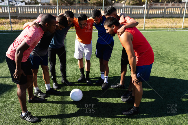 Multi ethnic group of male five a side football players wearing sports clothes training at a sports field in the sun, standing in huddle motivating before a game ball in the middle.