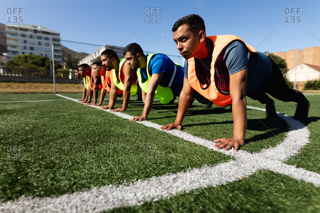 Multi ethnic group of male five a side football players wearing sports clothes and vests training at a sports field in the sun, warming up doing push ups in a row.
