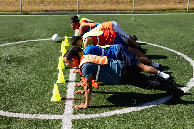 Multi ethnic group of male five a side football players wearing sports clothes and vests training at a sports field in the sun, warming up doing push ups in a row with ball and cones next to them.