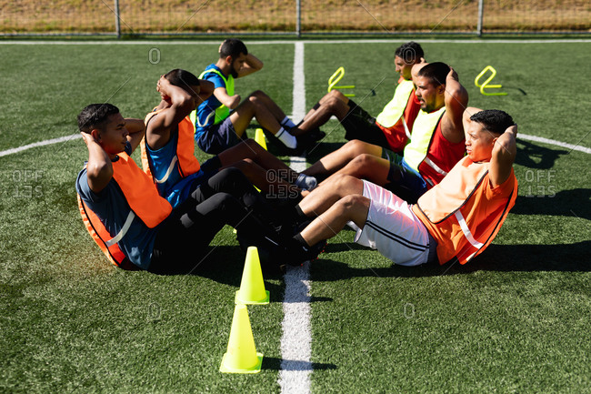 Multi ethnic group of male five a side football players wearing sports clothes and vests training at a sports field in the sun, warming up doing sit ups with cones next to them.