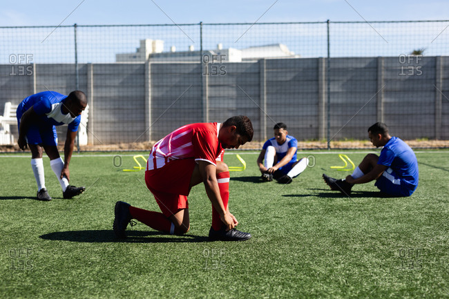Multi ethnic male five a side football players wearing a team strip training at a sports field in the sun, warming up tying their shoelaces.
