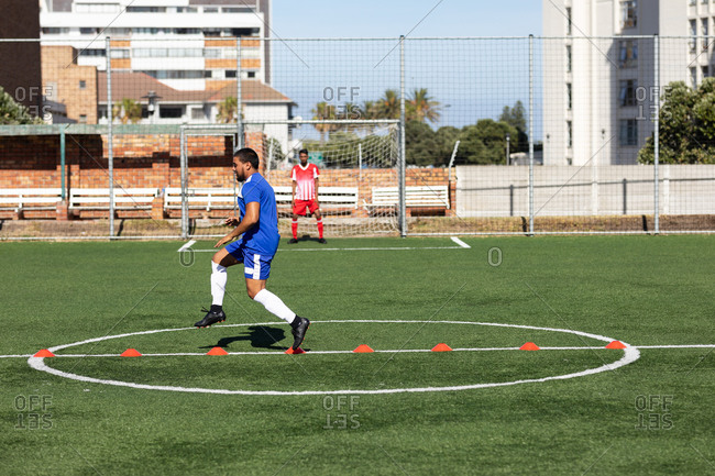 Mixed race male football player wearing a team strip training at a sports field in the sun, warming up jumping over cones another player standing in goal in the background.