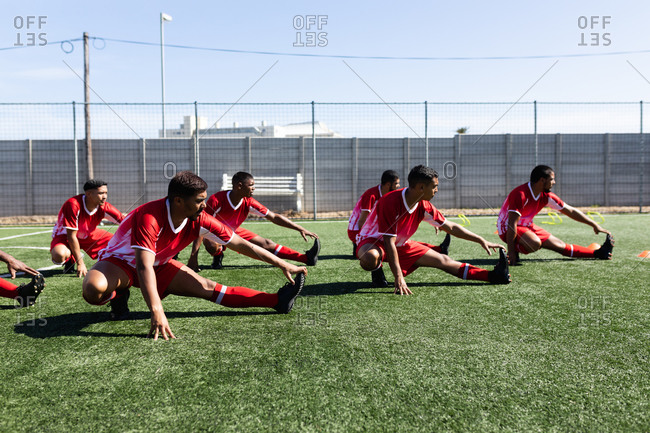 Multi ethnic team of male five a side football players wearing a team strip training at a sports field in the sun, warming up stretching.