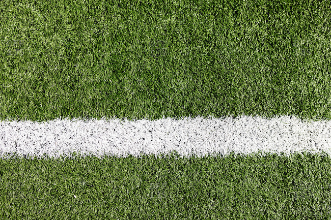 Close up of a white line drawn on a grass football pitch on a sunny day. Sports stadium football ground.