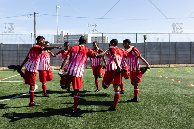 Multi ethnic team of male five a side football players wearing a team strip training at a sports field in the sun, warming up standing in circle supporting each other stretching.