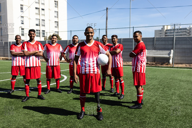 Portrait of multi ethnic team of male five a side football players wearing a team strip training at a sports field in the sun, standing holding a ball smiling to camera