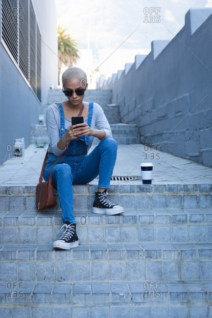 Mixed race alternative woman with short blonde hair out and about in the city on a sunny day, wearing sunglasses and denim dungarees, sitting on steps using smartphone. Urban digital nomad on the go.