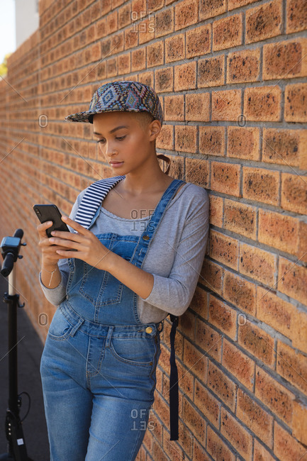 Mixed race alternative woman with short blonde hair out and about in the city on a sunny day, wearing denim dungarees and a cap, leaning against wall using smartphone. Urban digital nomad on the go.