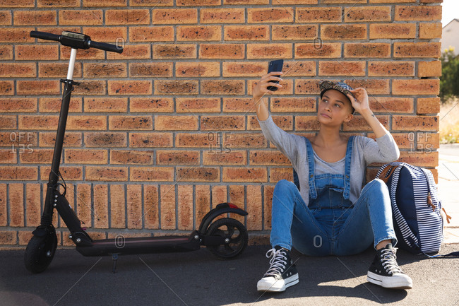 Mixed race alternative woman wearing a cap and dungarees out and about in the city on a sunny day, sitting against wall with her scooter taking a selfie with smartphone. Urban digital nomad on the go.