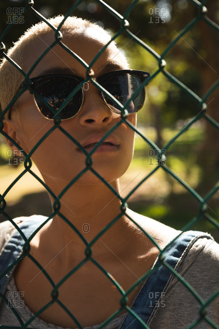 Portrait of mixed race alternative woman with short blonde hair out and about in the city on a sunny day, wearing sunglasses and looking through a chain link fence. Urban independent woman on the go.