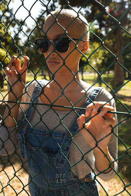Mixed race alternative woman with short blonde hair out and about in the city on sunny day, wearing sunglasses and denim dungarees, looking through chain link fence. Urban independent woman on the go