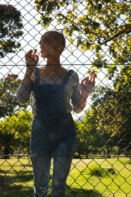 Mixed race alternative woman with short blonde hair out and about in the city on a sunny day, wearing sunglasses, denim dungarees, standing against chain link fence. Urban independent woman on the go
