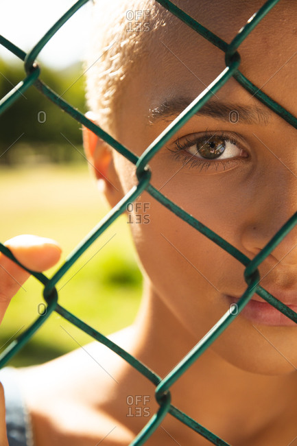Close up portrait of mixed race alternative woman with short blonde hair out and about in the city on a sunny day, looking through a chain link fence. Urban independent woman on the go.