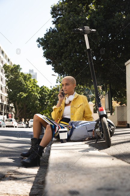 Mixed race alternative woman with short blonde hair out and about in the city on a sunny day, sitting on the curb using smartphone, e-scooter and a coffee beside her. Urban digital nomad on the go.