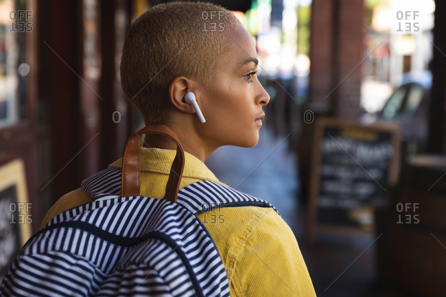 Mixed race alternative woman with short blonde hair out and about in the city on a sunny day, wearing wireless earphones and a backpack, walking and looking away. Urban digital nomad on the go.