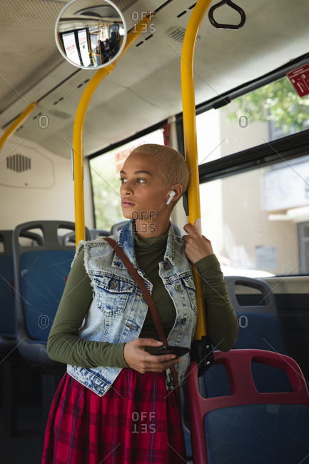Mixed race alternative woman with short blonde hair out and about in the city, standing on a bus using smartphone with wireless earphones and looking away. Urban digital nomad on the go.