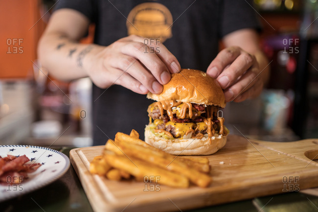 Crop ethnic male cook standing at counter in cafe with delicious burger on chopping board