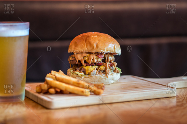 Delicious burger with cutlet and vegetables served on wooden cutting board with French fries in cafe