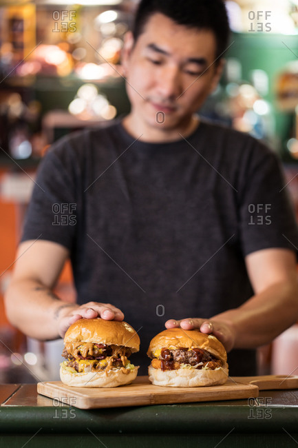 Crop ethnic male cook standing at counter in cafe with delicious burgers on chopping board