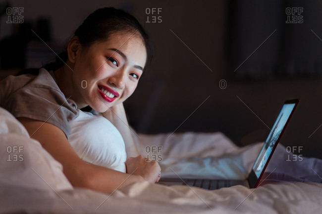 Side view of cheerful young ethnic female lying on crumpled bed sheet in front of open netbook and looking at camera in evening
