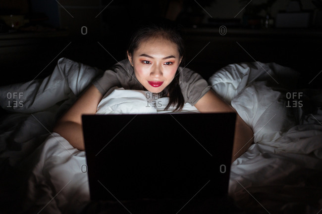 Young ethnic female lying on crumpled bed sheet in front of open netbook and looking at camera in evening