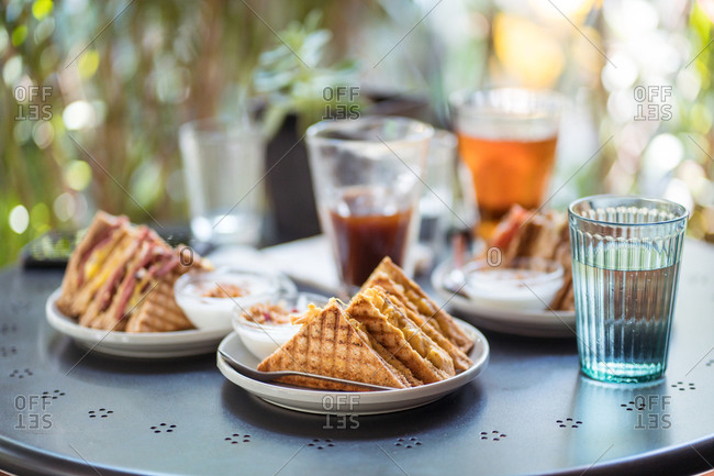 Delicious sandwiches on plate and refreshing drinks in glasses placed on table on summer terrace of cafe