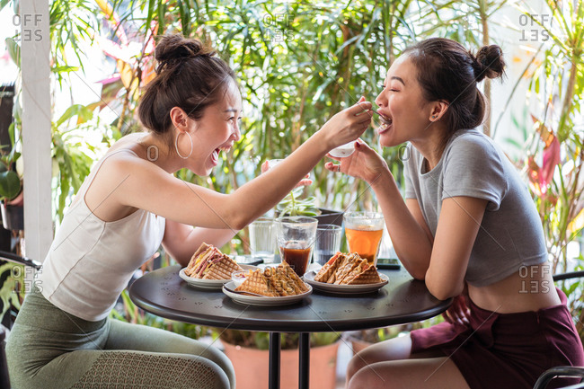 Side view of Asian girlfriends sitting at table in cafe and having fun while feeding each other with sweet treat and enjoying weekend together