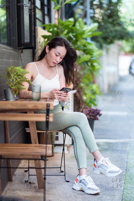 Ethnic woman using social media on smartphone in garden