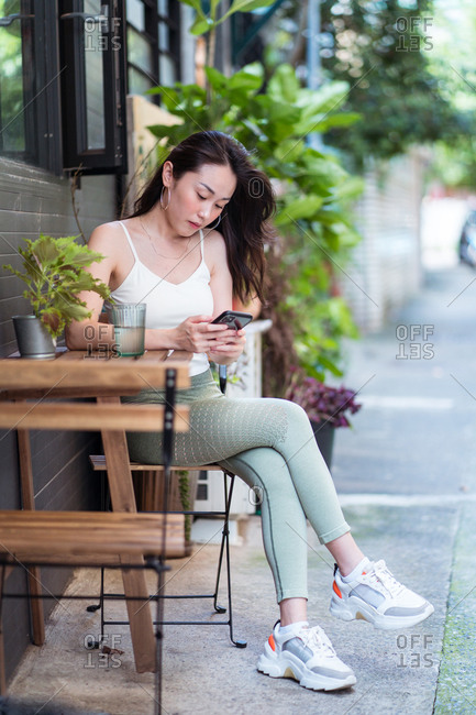 Ethnic woman using social media on smartphone in garden