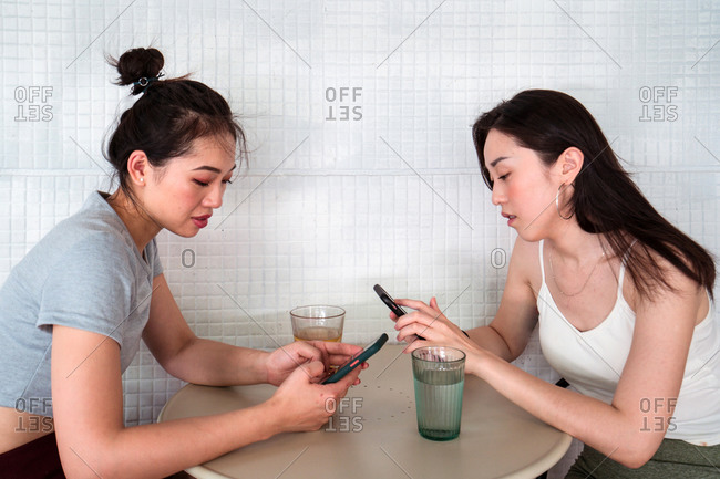 Side view of young calm Asian female friends in casual wear sitting with crossed legs at table with glasses of water while using social media on cellphones in cafe