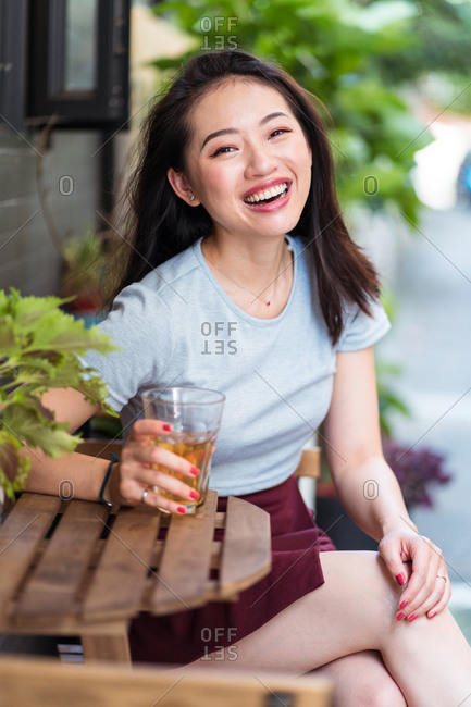 Young Asian female sitting at counter with fresh drink in cafe and enjoying weekend and looking at camera