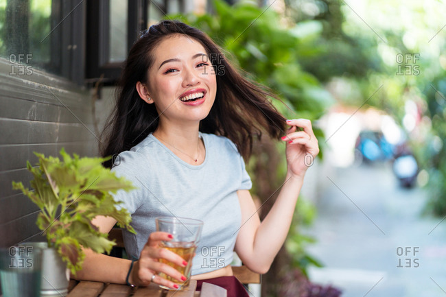Young Asian female sitting at counter with fresh drink in cafe and enjoying weekend while touching hair and looking at camera