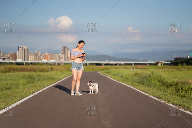 Fit Asian woman in casual clothes surfing internet on cellphone while standing on empty road with American Cocker Spaniel near grass under cloudy sky in summer in city