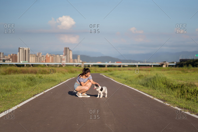Asian female in casual wear cuddling gently American Cocker Spaniel while squatting on walkway between grass behind skyscraper under cloudy sky looking away