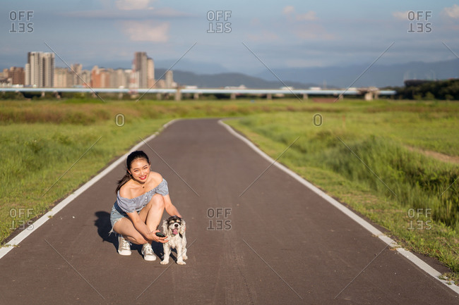 Asian female in casual wear cuddling gently American Cocker Spaniel while squatting on walkway between grass behind skyscraper under cloudy sky looking at camera