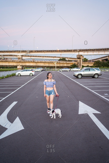 Thoughtful Asian female in denim shorts walking American Cocker Spaniel by leash on asphalt road with marking near cars parked on parking lot under serene sky and looking away
