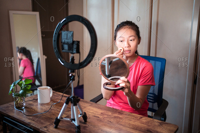 Young Asian woman in casual wear holding mirror and applying foundation on face while recording video tutorial for beauty blog at home workplace with ring light and camera
