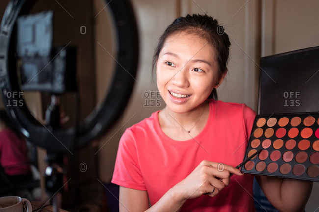 Positive young Asian woman demonstrating colorful makeup palette while recording beauty vlog video in room with ring light