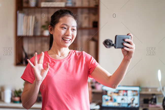Happy young Asian female in casual clothes smiling and greeting subscribers while shooting video for social media with smartphone at home