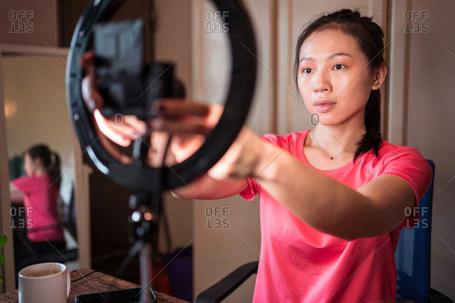 Young Asian female in casual outfit with manicure using camera and ring light while shooting video tutorial for beauty vlog in studio