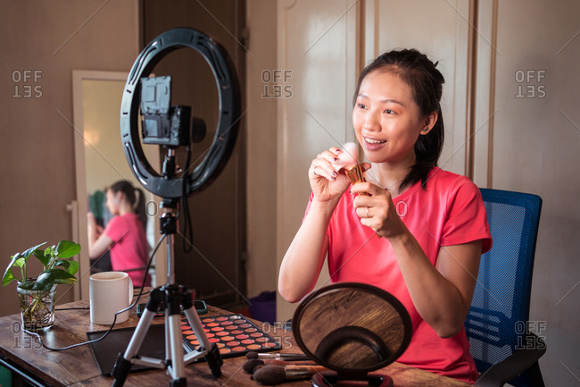 Cheerful young Asian female in casual outfit demonstrating bunch of various types of brushes for makeup while recording beauty video vlog at home