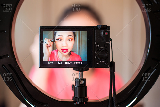 Positive young Asian beauty blogger with bright makeup applying mascara on eyelashes while recording video for new post with camera and ring lamp