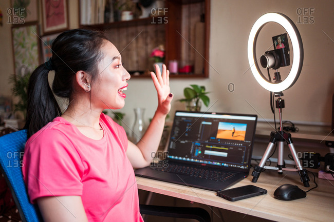 Side view of positive young Asian female beauty influencer with bright makeup waving hand and talking with subscribers while sitting at table with gadgets and ring light and filming video on camera