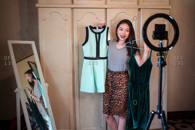 Positive young Asian female showing stylish dresses and giving advice during shooting video for fashion vlog while standing in front of tripod with camera and ring lamp at home