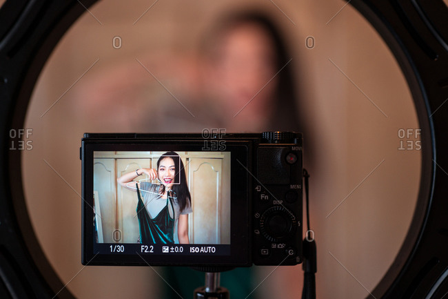 Cheerful young Asian female blogger seen on camera display recording content for fashion channel on social media and demonstrating glamorous dress